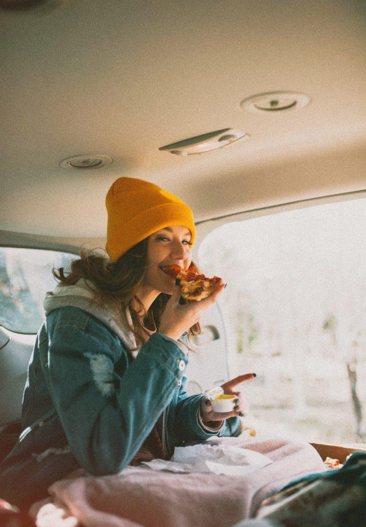 Mädchen isst Pizza im Auto