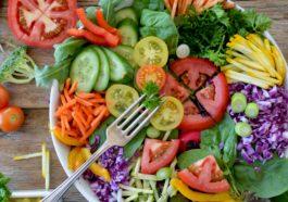 Salatschlüssel auf einem Holztisch mit und umgeben von gleichmäßig geschnittenem Gemüse