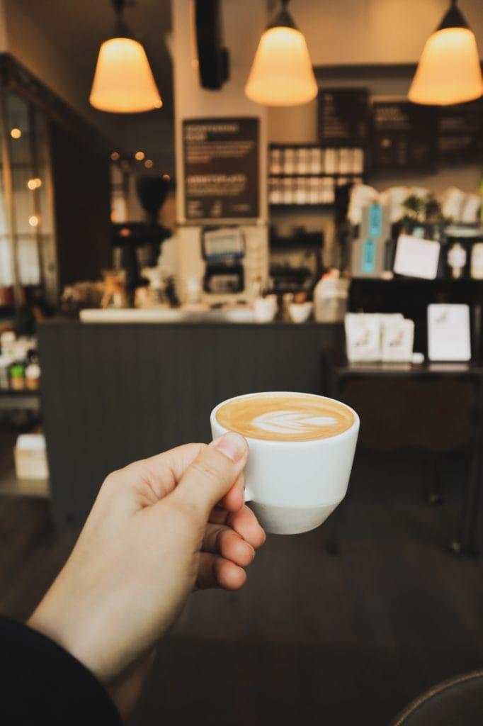 Frau hält Kaffeetasse mit Cappucchino in einem Café