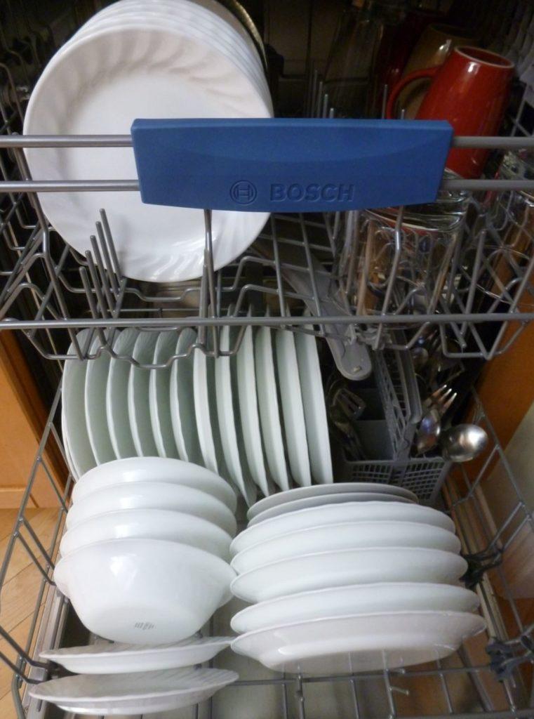 Offene Einbauspülmaschine mit Tellern und Geschirr drin