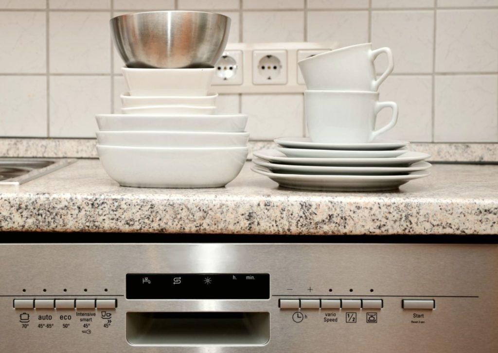 Spülmaschine mit Geschirr auf der Arbeitsplatte darüber