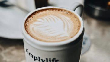 Einfacher Milchkaffee in einer Tasse mit der Aufschrift simplylife