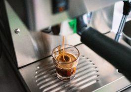 Kaffepadmaschine mit einem Glas Espresso darunter