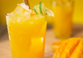 Mangosaft mit Zitrone und Eiswürfeln im Gas auf einem Tisch mit Mangos und Zitronen