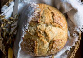 Rundes selbstgebackenes Brot auf einem Tisch in einem Korb