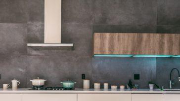 Rustikale Küche mit Holzelementen, blauen Lichtern und silbener Dunstabzugshaube