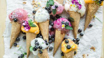 Verschiedene Eissorten in Waffeln mit Blaubeeren und Zuckerkugeln auf einem Tisch